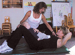Jamie Levine shows new mom an abdominal exercise with baby