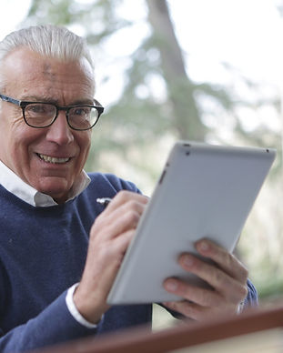 man-in-blue-sweater-holding-white-tablet