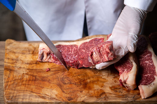 front-view-of-butcher-cutting-meat-in-wh