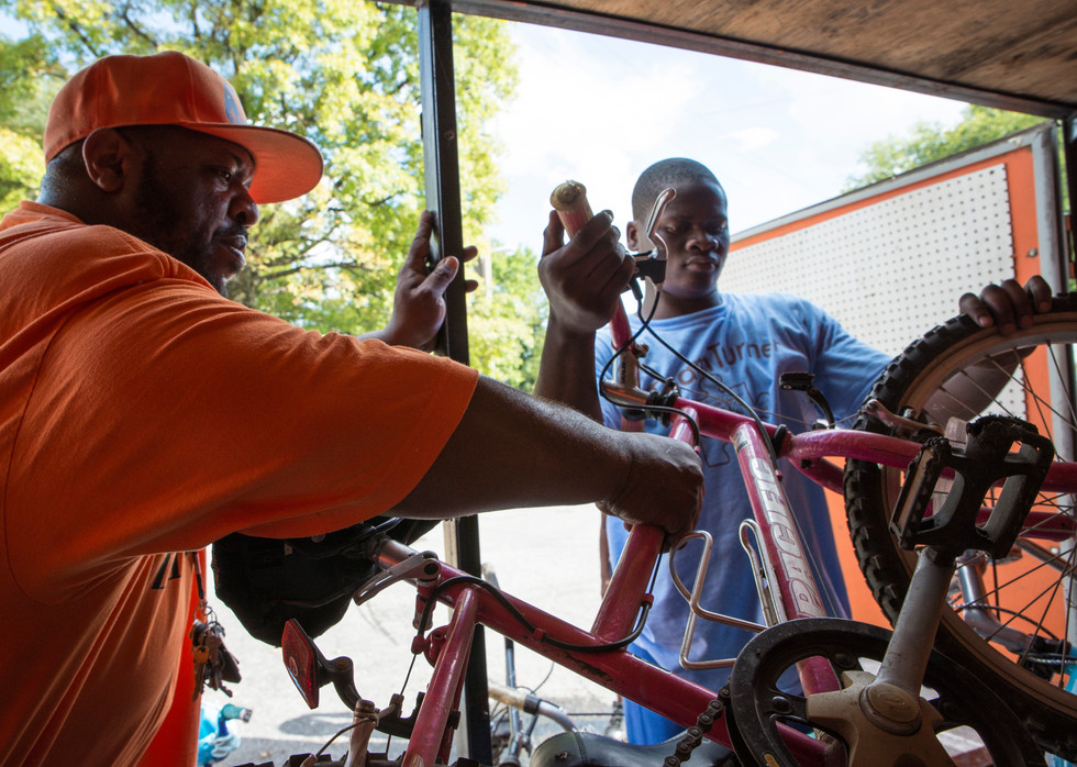 """Sept. 4, 2018, Key and one of his original """"Riders"""" Abdi Abde, 17, unload some bikes at the nearby Hillside Apartments. Adan has ridden with Key for about 8 yrs."""