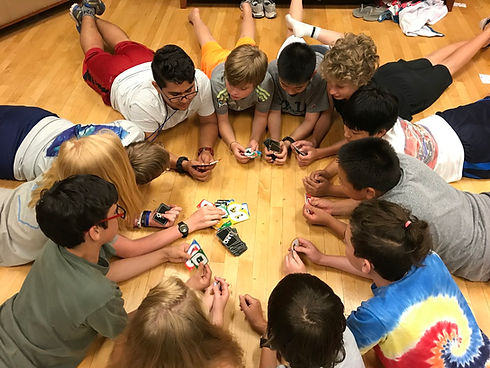 A group of campers playing a game of UNO