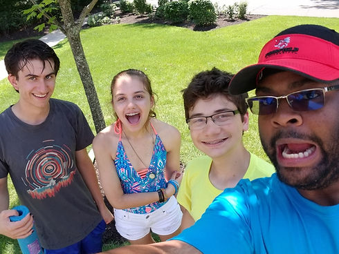 An Emagination Tech Camp counselor taking a selfie with campers