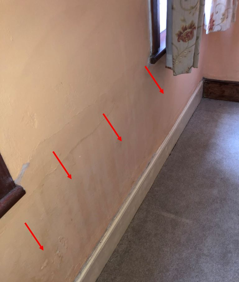 Damp staining to bedroom wall facing the front elevation