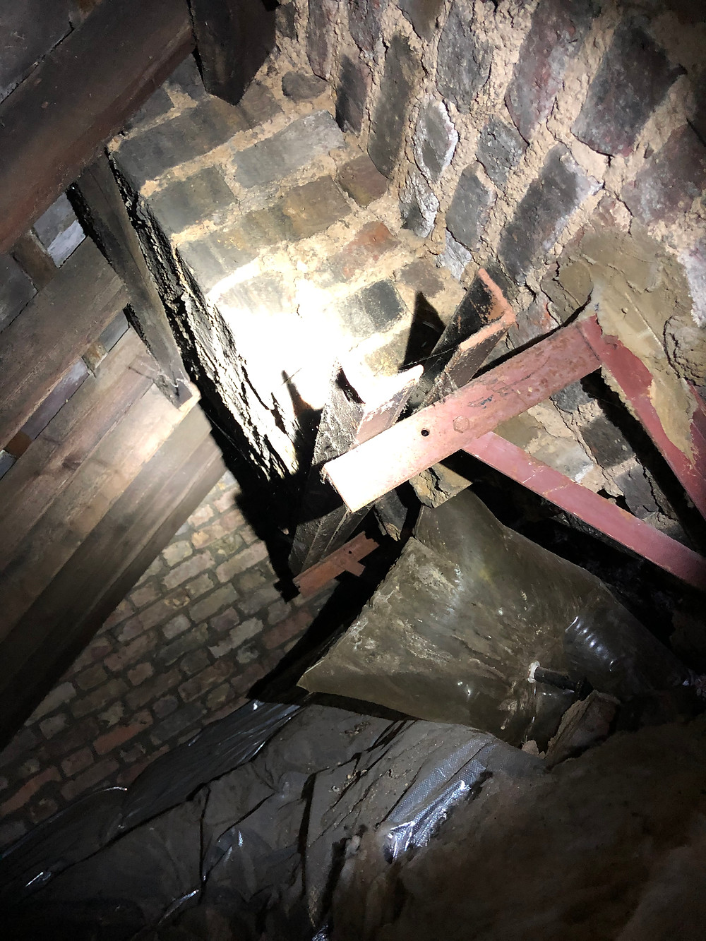 A old chimney stack supported via a gallows bracket within the loft space.