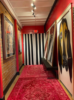 Art filled hallway with doggie door entrance to the ADA bathroom, portrait by Jules Muck of her beautiful bloodhound Dada