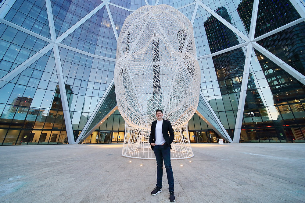 "Ken King stands in front of the ""Alice Head"" in downtown Calgary, Canada."