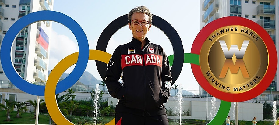 Shawnee Harle stands in front of the olympic rings