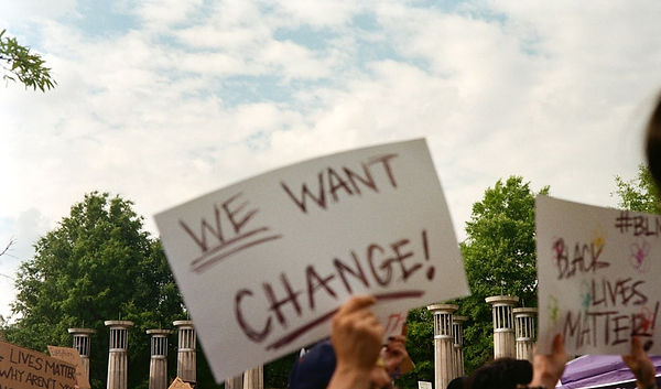 """hands at a protest holding up a sign that reads """"We Want Change"""""""