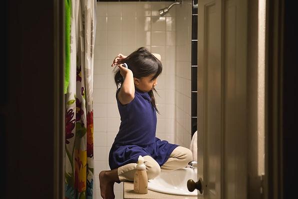Asian girl looking in a bathroom mirror