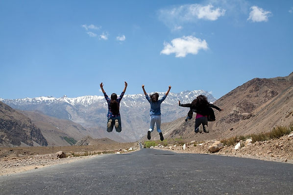 Three people jumping in front of a mountain