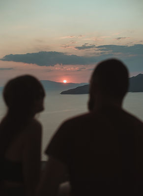 two figures silhouetted against the ocean