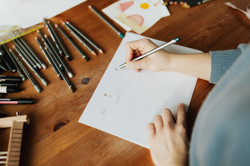 crop-young-craftswoman-drawing-on-paper-