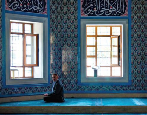 Man kneeling in mosque.png
