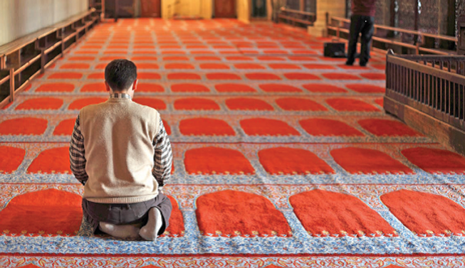 Man praying in mosque with red carpet.pn