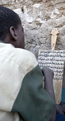 Boy writing in Arabic.png