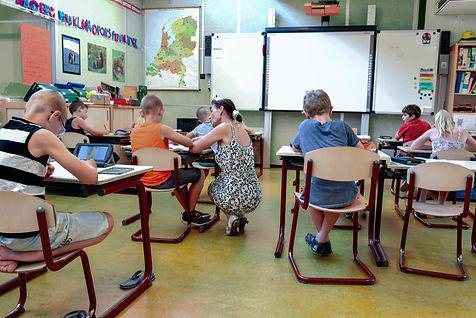 children-sitting-on-brown-chairs-inside-