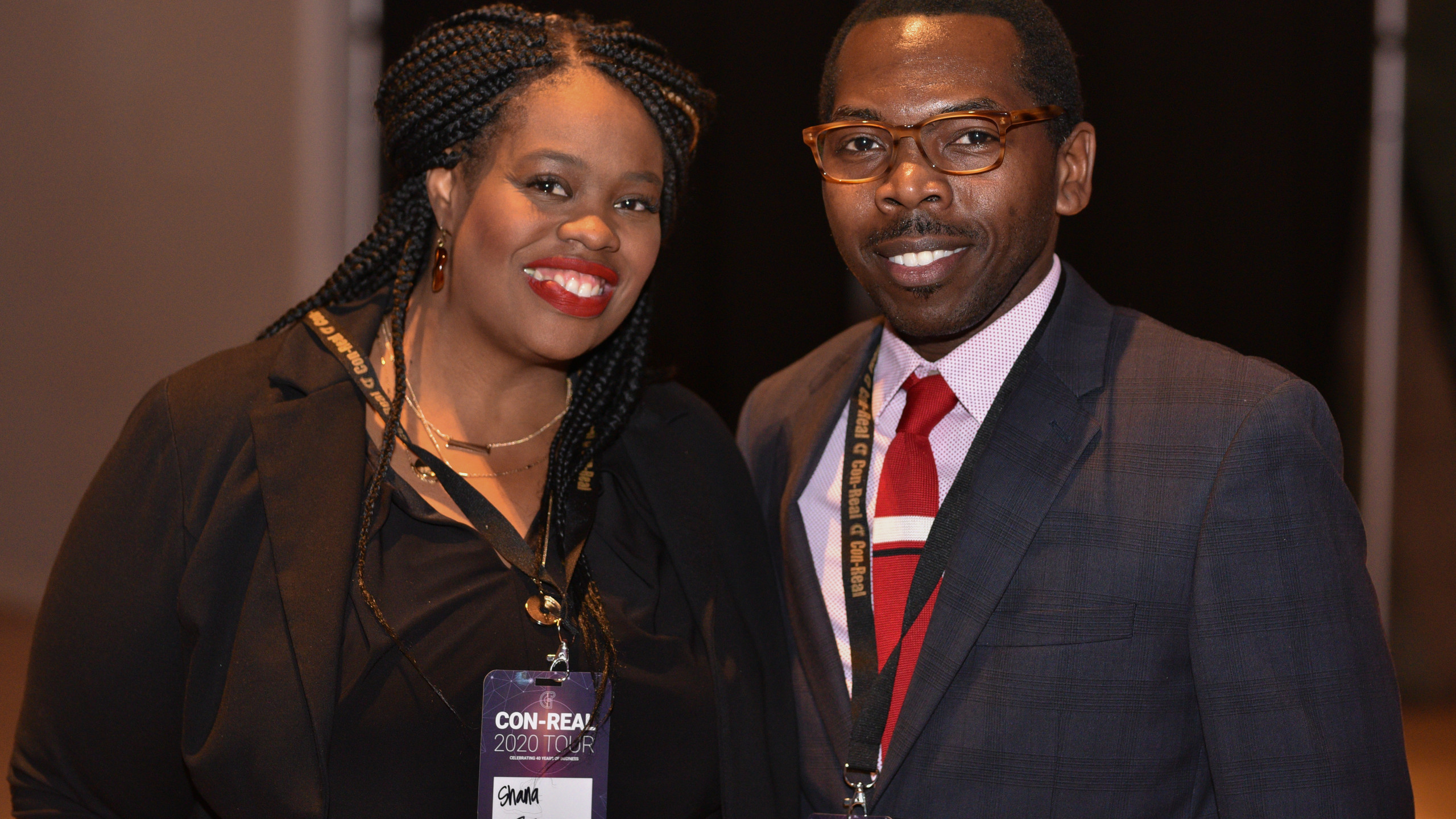 A black woman and black man in professional attire, smiling