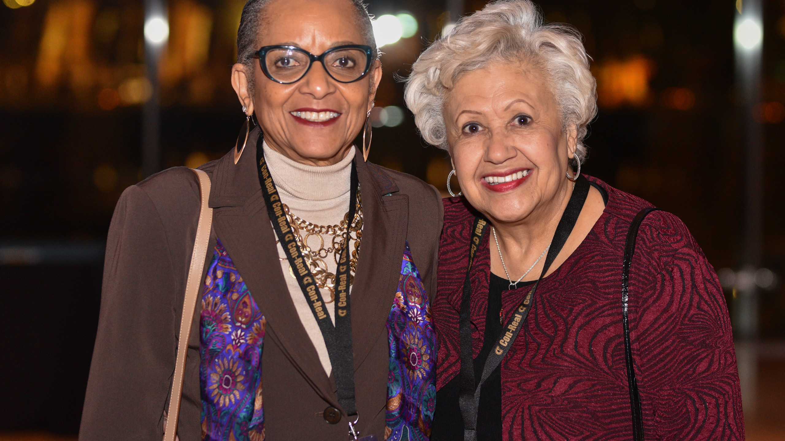 Two older black women, one with glasses, smiling.