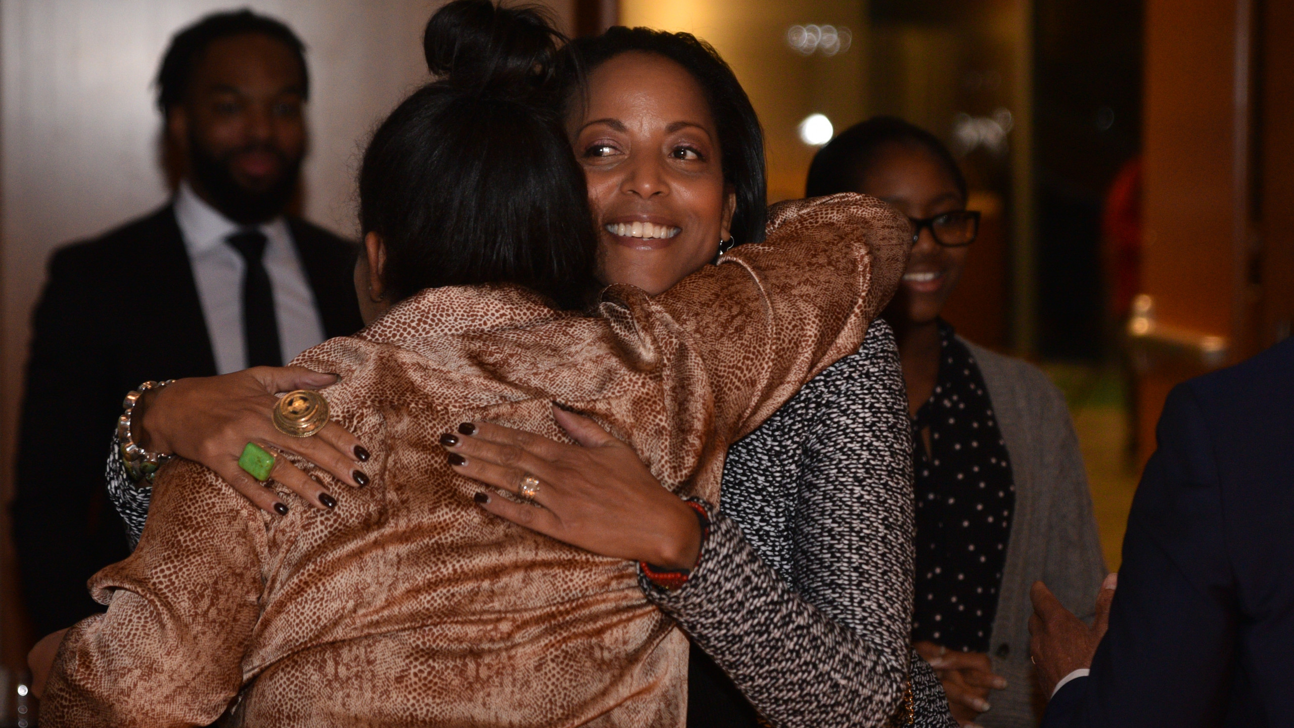 Two black women hugging at the event