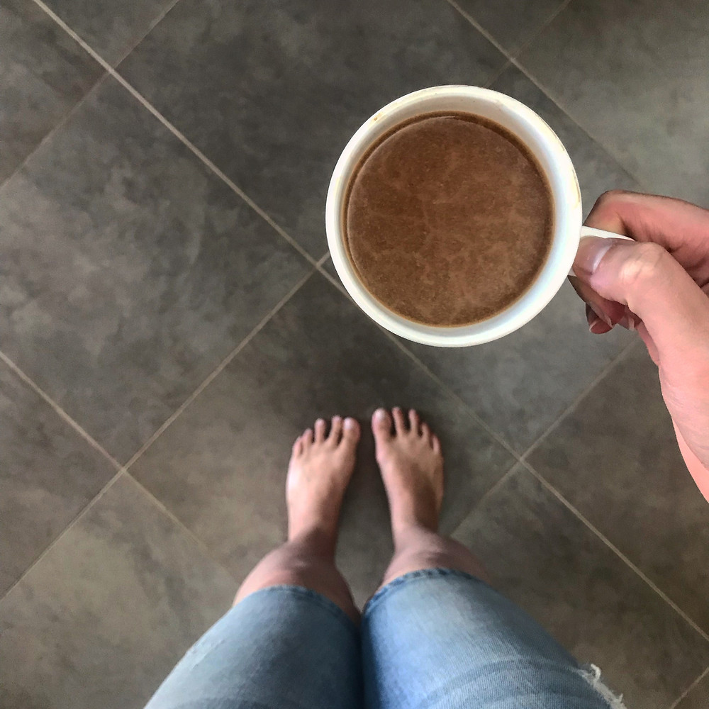 Barefoot. Indoors. Coffee in a porcelain mug. Luxury.