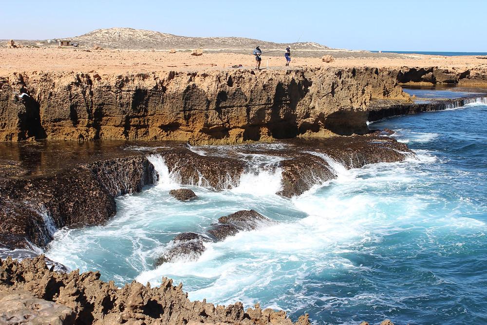 Brave fishermen over surging waves, relentlessly pounding the rock.