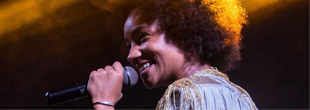 Smiling woman singing into a microphone