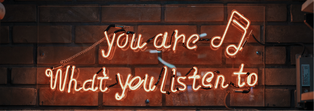 neon light on brick wall saying 'you are what you listen to'