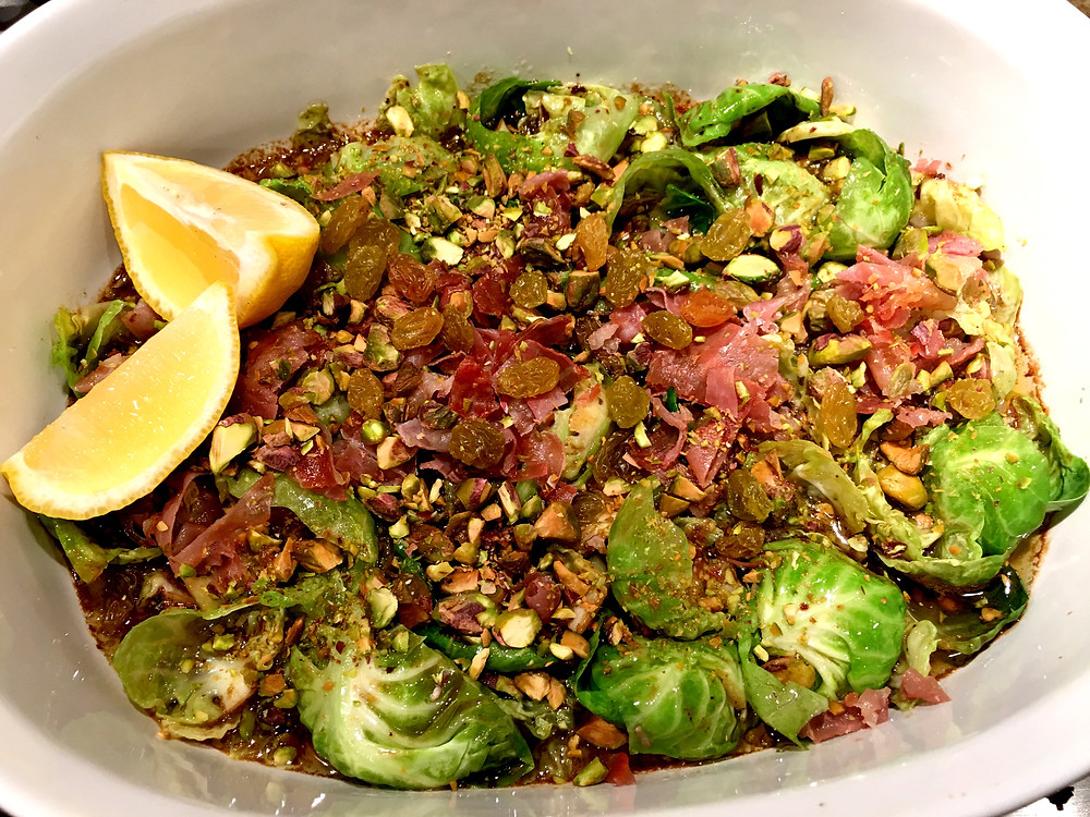 Beyond awesome Brussels sprouts are served with slices of fresh lemon. Enjoy!