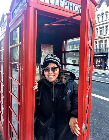 Woman comes out of a traditioal red phone booth in London, England.