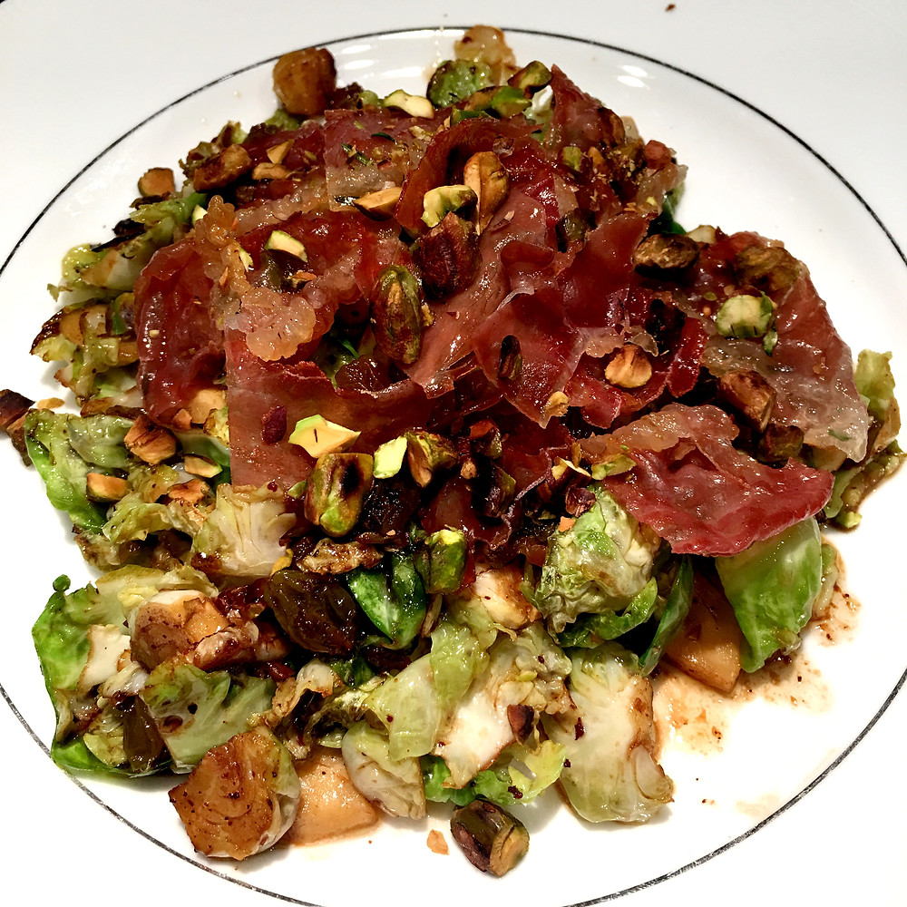 Brussels sprouts leaves sauteed in a brown butter sauce with crispy prosciutto, dried fruit, and toasted pistachios