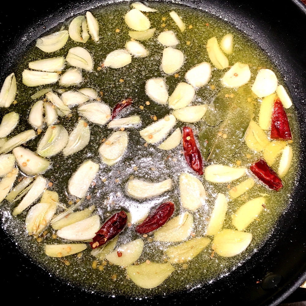 Sliced garlic and red chilis in oil in a frying pan