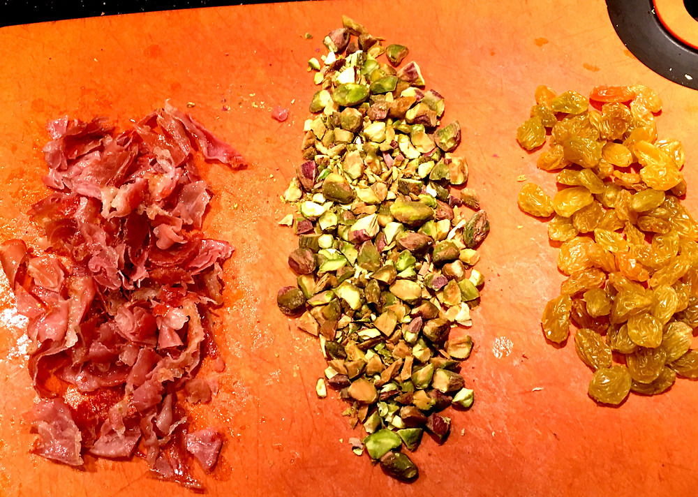 Creative toppings make this dish full of flavors. Pictured here: crisped prosciutto, toasted pistachios, and dried fruit.