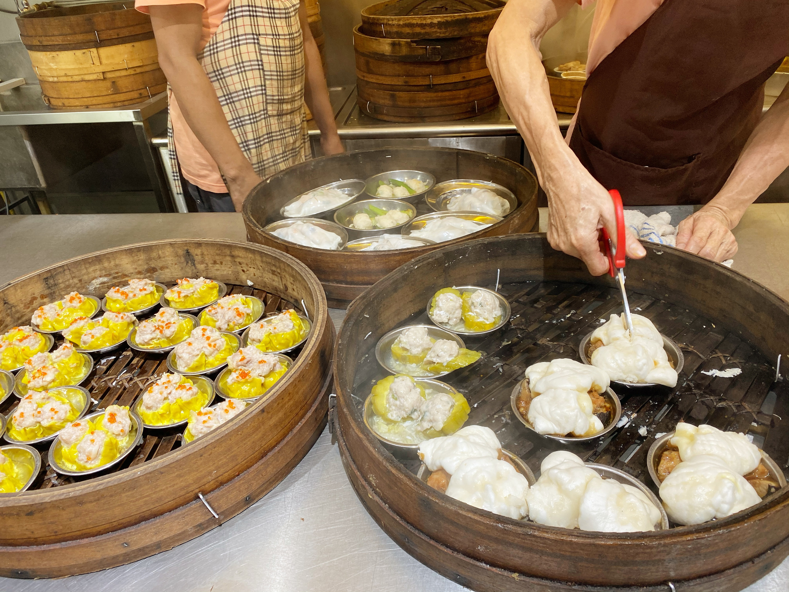 Large bamboo steamers filled with dim sum foods including pork shu mai, dumplings, and steamed bao
