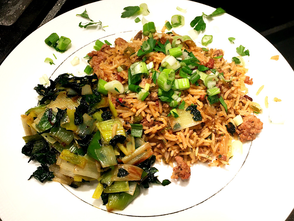 New Orleans Dirty Rice topped with scallions and served with sauteed kale and leeks