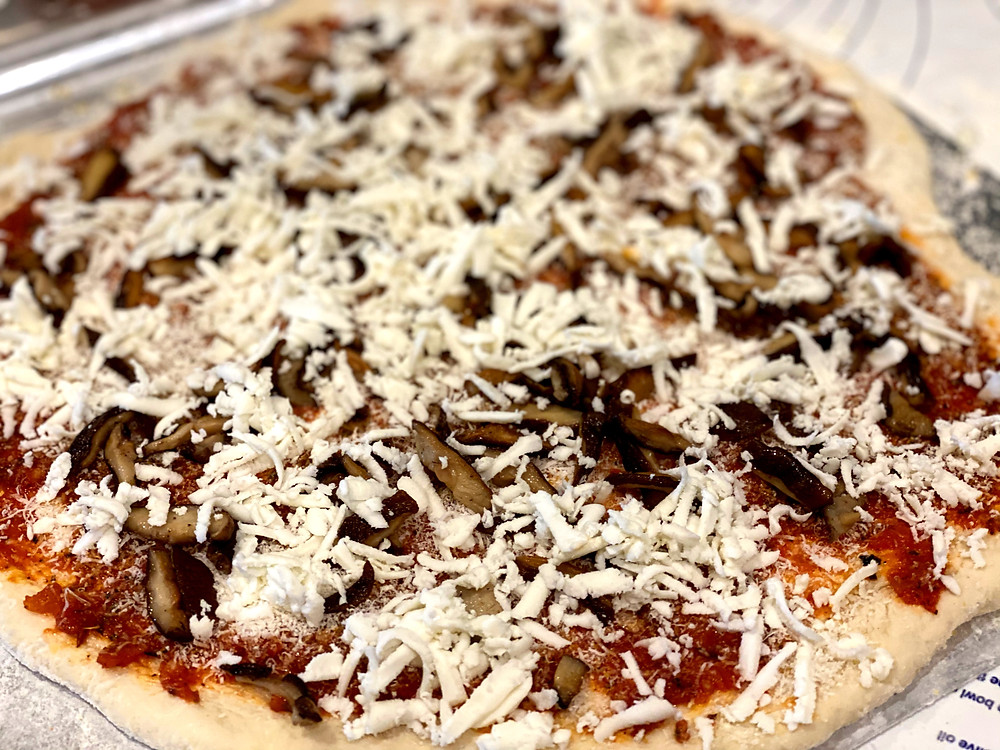 Homemade pizza about to go in the oven. We made the sauce and the dough from scratch and topped it with some sautéed shiitake mushrooms.