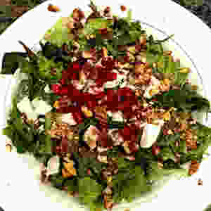 Salad with assorted greens, spicy pecans, pomegranate seeds, and infused goat cheese