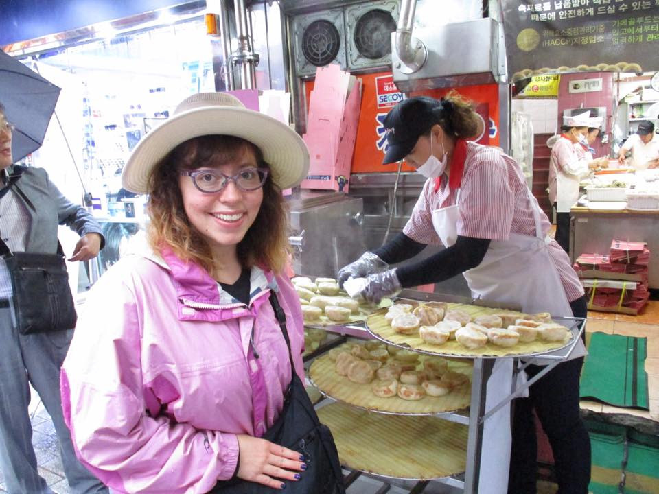 woman in pink rain coat about to purchase kimchi-filled dumplings in the Namdaemun area of Seoul, Korea