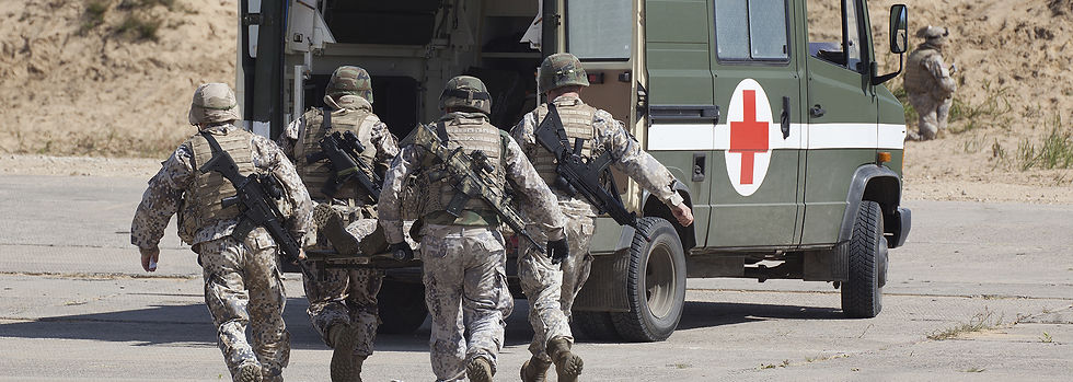 Soldiers walking towards ambulance