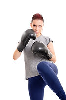 Portrait of a beautiful young serious girl with boxing gloves lifting her knee, isolated o