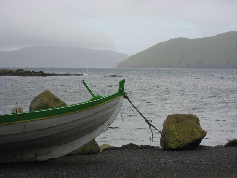 Traditionelles färöisches Boot, weißer Rumpf und grüne Akzentuierung. Es ist angeleint und steht an Land.
