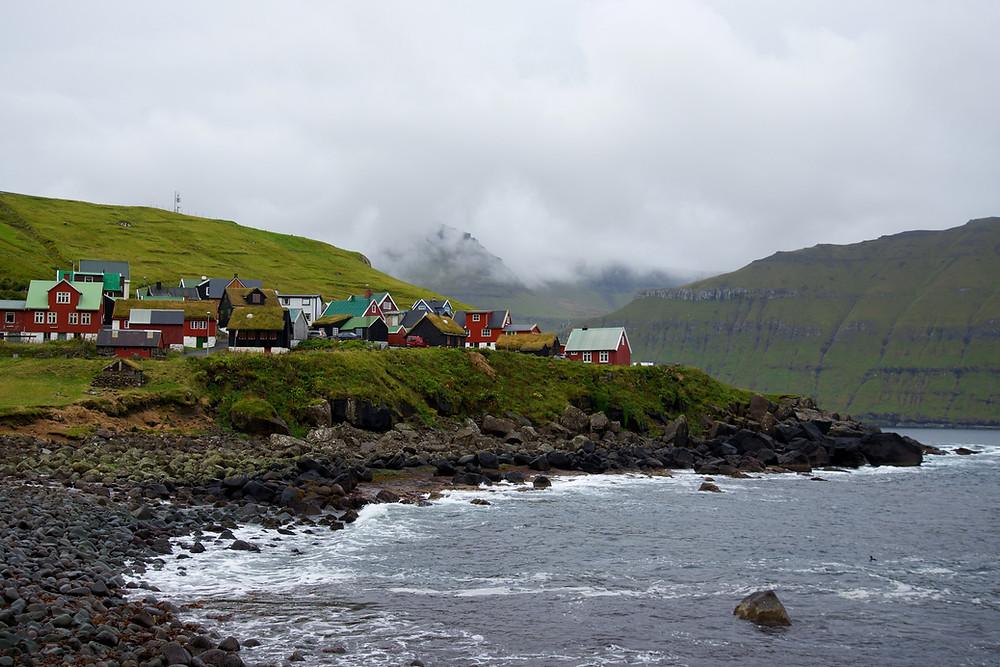 Färöisches Dorf an der Küste. Die Häuser sind bunt bemalt und im Hintergrund ist ein nebenverhangener Berg zu sehen.