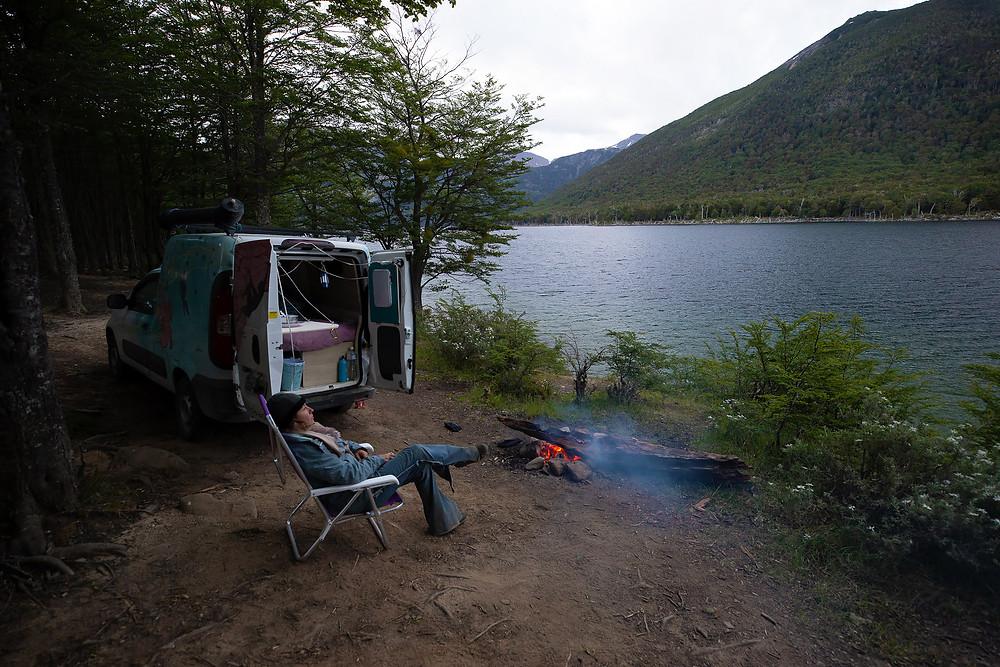 À beira de um lago está estacionado o motorhome construído em uma Fiorino. A viajante Camila Caggiano está sentada em uma cadeira dobrável e na sua frente há uma fogueira acesa. Ao fundo, atrás do lago há uma bela montanha.