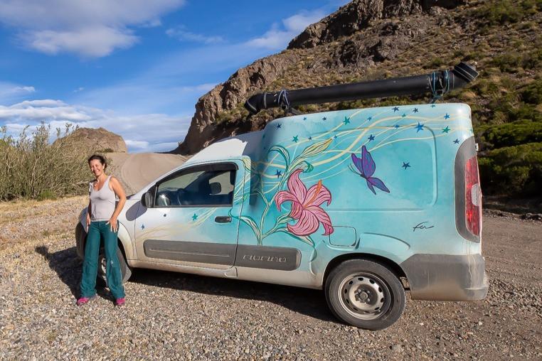 Em uma estrada de pedrinhas, aparece um paredão rochoso, céu azul e a viajante Camila Caggiano ao lado do seu motorhome, uma Fiorino chamada Safira