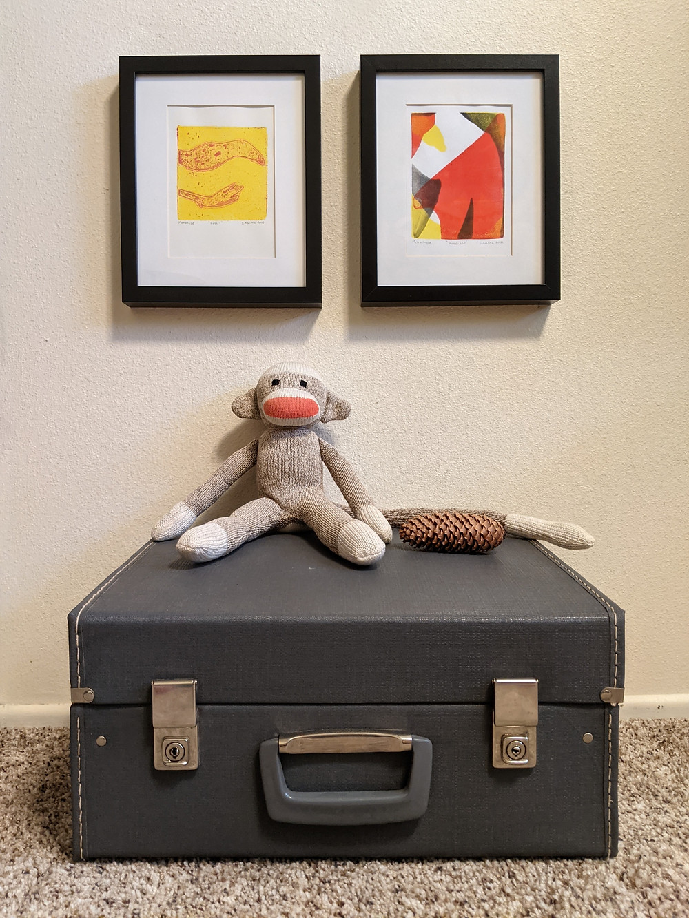 WxH shows how art can be hung at kids eye level with two prints and a monkey toy on a suitcase