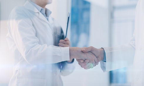 medical professionals shaking hands during the healthcare onboarding process.