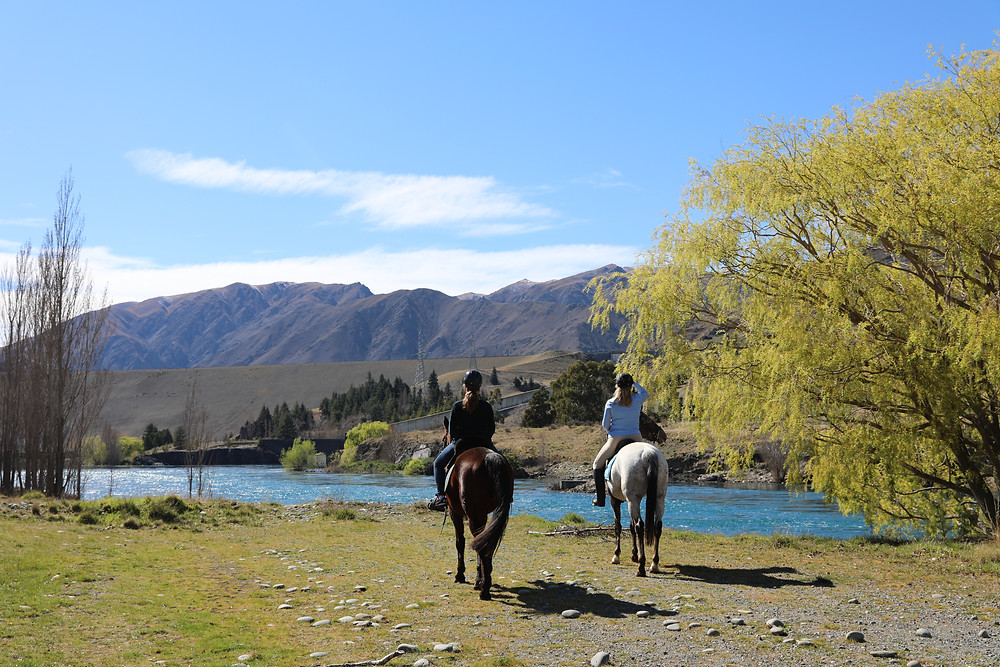 Two horses and riders in front of river and mountains