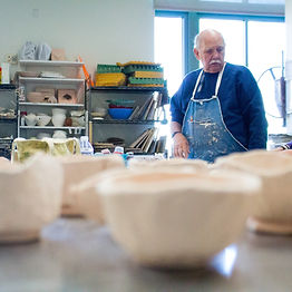 Gary Huntoon, a white man with a white mustache and glasses, wears a blue sweatshirt and denim apron in SAM's ceramic studio. Drying pottery can be seen out-of-focus in the foreground. Shelves of ceramics supplies can be seen in the background, next to the window.