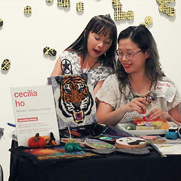 Cecilia Ho, a Chinese woman, smiles at her daughter as they set up a felting booth in the Museum. A felted portrait of a tiger sits on a easel next to them, along with other felting supplies and a sign with Cecilia's name on it. An art installation of small black-and-yellow circles can be seen in the background.