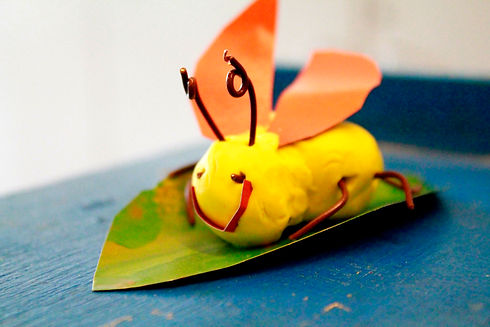 A smiling insect made of yellow clay sits on a green leaf