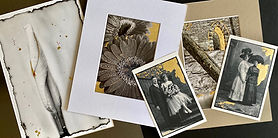 An arrangement of several black-and-white photographs with gold leafing lay on a tabletop. From left to right: daisies, an antique photo of a bride and groom, an abstract image, and another antique photo of two women, one in a white dress and one in a dark dress.
